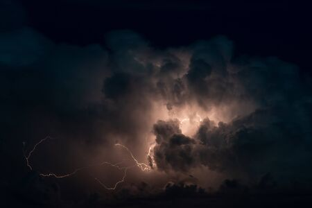 Thundercloud with beautiful lightning bolts in night sky 写真素材