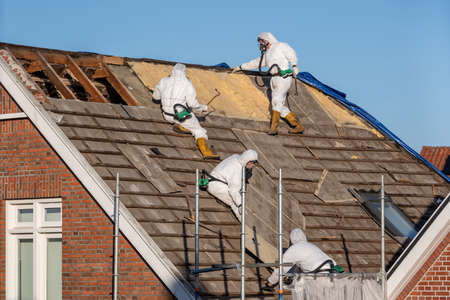 Professionals in protective suits remove asbestos-cement roofing underlayment