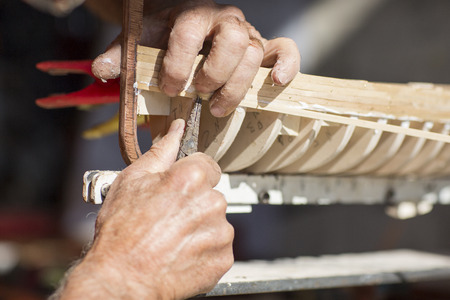 old man working on creating a wooden model of a boat