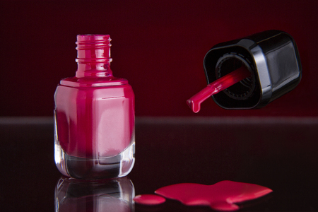 closup of a bottle of red nail polish with brush and spilled nail polish