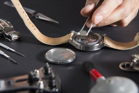 Nahaufnahme des Ersetzens einer Uhrenbatterie durch Uhrmacherwerkzeuge