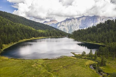 photo taken with drone above a mountain lake immersed in the woods with shelter and alps in the background Banco de Imagens