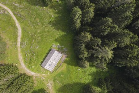 aerial photo of a mountain house surrounded by greenery with a forest of fir trees and people walking along the path Banco de Imagens