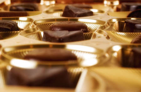 Assorted chocolates in shiny gold case - close up photo