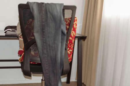 Pair of jeans and clothes draped over the back of a chair