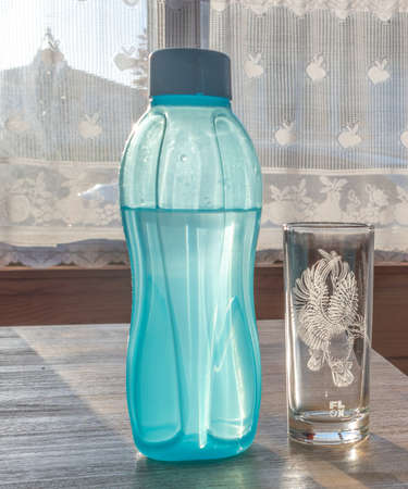 Blue plastic water bottle and glass standing on a wooden table top against a bright sunny background