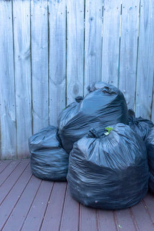 Vertical image of three black plastic garbage bags packed and ready to take out sitting on the deck against a wooden fence Stock Photo