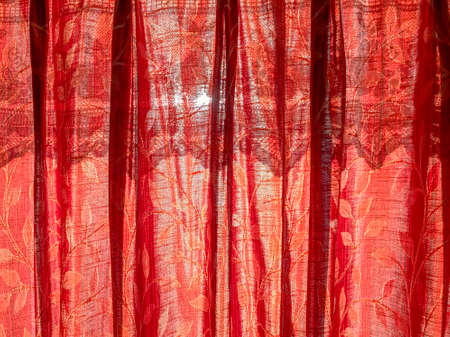 Vertical image of a red curtains drawn against the sunlight glowing in the background 写真素材