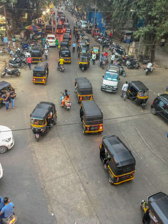 Mumbai India, Saturday Jan 13th 2018 - Black and yellow auto-rickshaws clog up a busy intersection driving any which way during the day