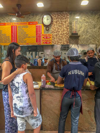 Kolkata India, Thursday Jan 11th 2018 - a woman and boy look on as their order of mutton kathi rolls is being prepared at Kusum's Kathi Roll stall
