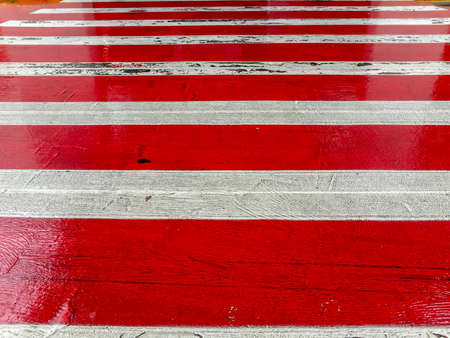 Horizontal perspective of red and white painted zebra crossing - abstract design Stock Photo