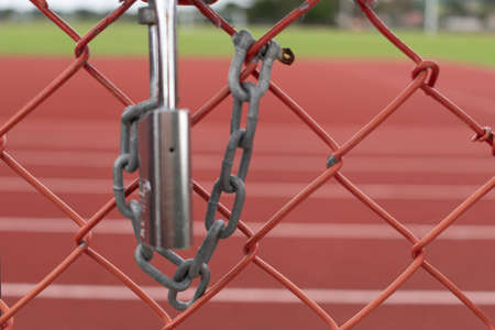 Silver lock and chain on metal fence securing red surface race track Banco de Imagens