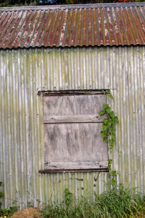 Boarded up window of old rusty shed left abandoned