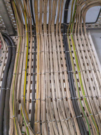 Electrical wiring cables tacked onto metal base leading downwards