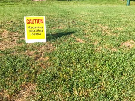 Caution sign indicating machinery operating in the area sitting on the grass of a public park during the day in the Auckland New Zealand
