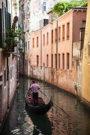 punting: Venetian gondolier gondolas punting through green waters of the canal in Venice Italy Stock Photo