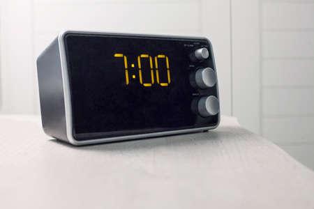 Digital alarm clock with yellow digits showing seven oclock