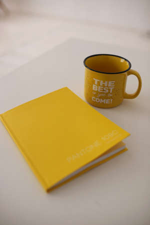 A yellow diary and a yellow mug with the words the best is yet to come lie on a white table in a white room. Diary and yellow mug. The color of the year is yellow. Selectiv focus.