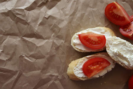 White bread sandwiches, spread with cottage cheese and ripe juicy tomatoes. With place for text. On a brown crumpled paper background.