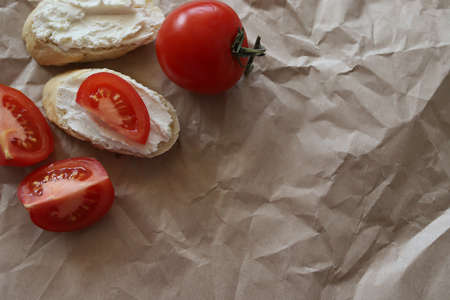 Spreadable bread with curd cheese on a mint paper background with slices of ripe juicy tomato. A whole tomato next to the sandwiches. Space for text Bottom.