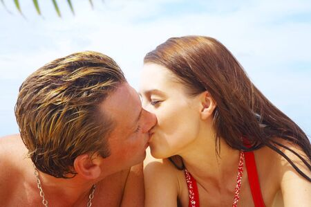 buss: a portrait of attractive couple having kiss on the beach