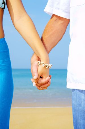 view of a young couple holding hands on the beach