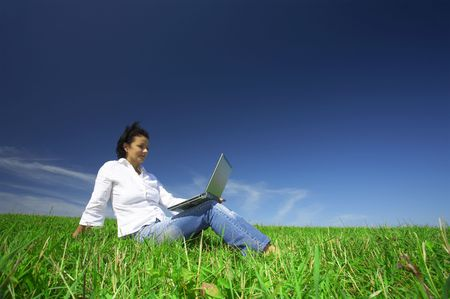 view of nice young girl sitting with laptop  on summer green grass