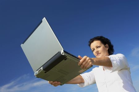 view of nice young woman with laptop on blue back Stock Photo