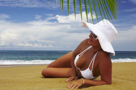 solter�a: agradable vista de la mujer en lounging playa tropical en panam� blanco y bikini