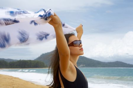 laze: View of nice young woman with wind-blowing sarong  Stock Photo