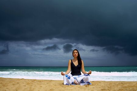 solter�a: vista del yoga practicante de la mujer joven agradable en la playa tempestuosa
