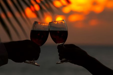 clang: view of two human�s hand with wineglasses during sunset Stock Photo