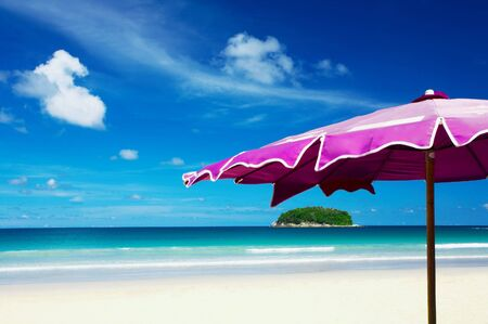 view of nice violet umbrella and small tropic island in the distance