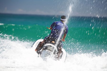 fiercely: view of jetski rider fiercely struggling with ocean wave