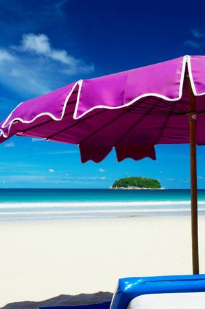 laze: view of nice violet umbrella and small tropic island in the distance Stock Photo