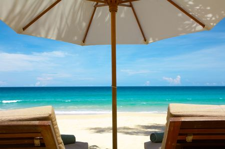 laze: view of two nice chairs and umbrella on tropical beach