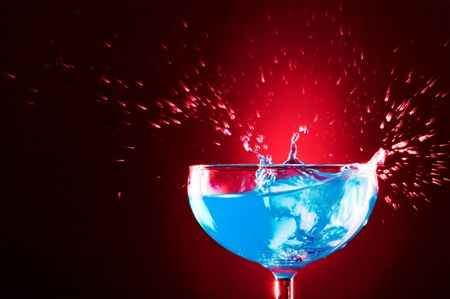 view of  cocktail glass with blue Curacao splashing over   photo