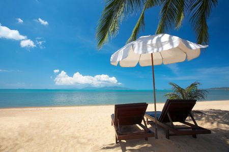 laze: view of two chairs and  white umbrella on the beach