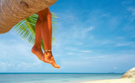laze: view of womans legs hanging from the palm Stock Photo