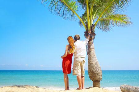 un portrait des couples attrayants ayant la date sur la plage