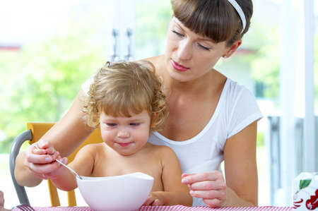 Portrait of young woman feeding her  daughter photo