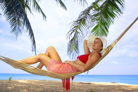 lounging: view of nice woman lounging in hammock in tropical environment