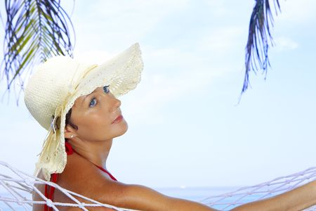 calmness: view of nice woman lounging in hammock in tropical environment