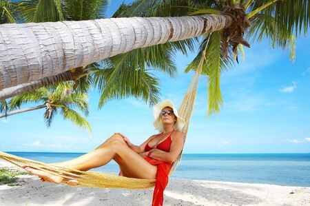 view of nice woman lounging in hammock in tropical environment photo