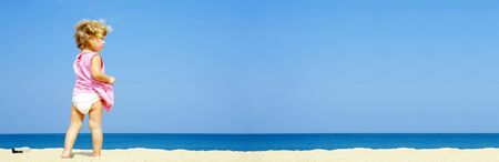 Portrait of blond blue eyed having fun on the beach. Banner lots of copy space
