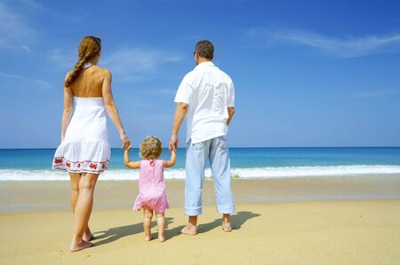 cerulean: Portrait of young family having fun on the beach Stock Photo