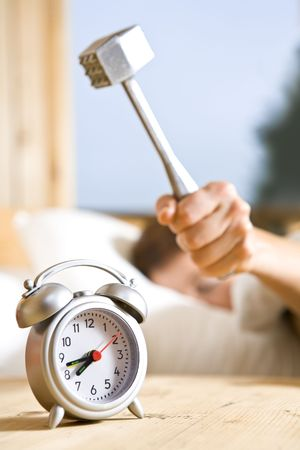 molest: Close up view of big kitchen hammer is ready to crash alarm-clock