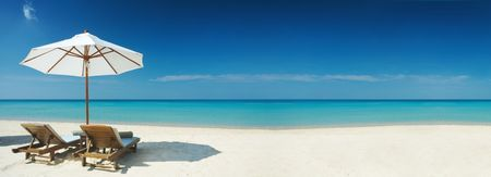 Panoramic view of two chairs and white umbrella on the beach. Banner, lots of copy space