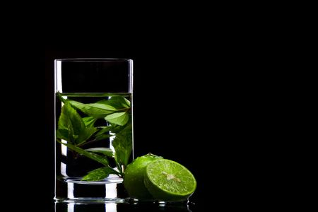 View of glass filled with green tea and some limes aside photo