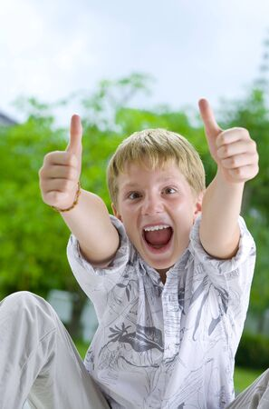 man thumbs up: Portrait of young boy giving his thumbs up